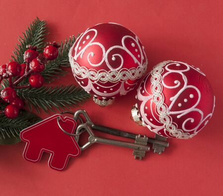 Christmas decorations: decorative house and key to the lock on red paper background, concept of finance and housing loans Zdjęcie Seryjne