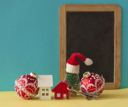Christmas decorations: decorative house with key to the lock and Santa hat on  background, concept of finance and housing loans