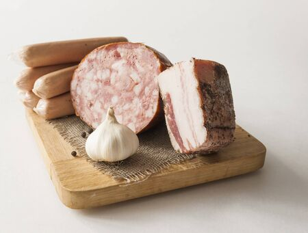 sausage with lard on wooden cutting board over white background. Top view Zdjęcie Seryjne