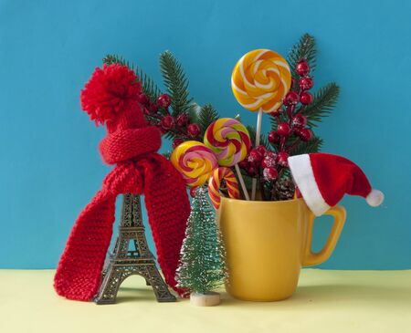 Christmas decoration with  statue in red scarf and hat  on colorful paper background. Holiday background with space for text