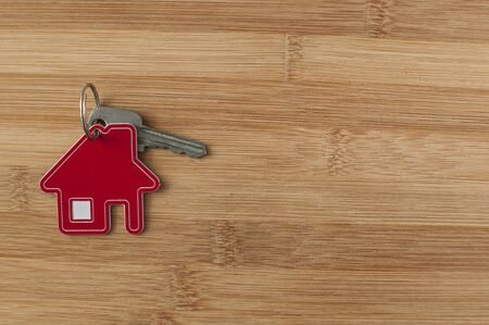 Close up of house keys on a house shaped keychain on wooden background. Concept for real estate, moving home or renting property Stock fotó - 137890188