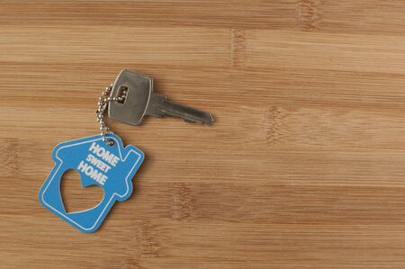 Close up of house keys on a house shaped keychain on wooden background. Concept for real estate, moving home or renting property Stock fotó