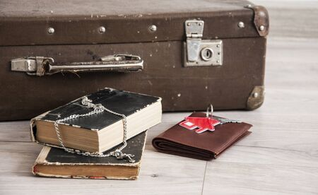 Vintage luggage with blank space of photo frame and stack old books on wooden table. Journey memory concept. Top view