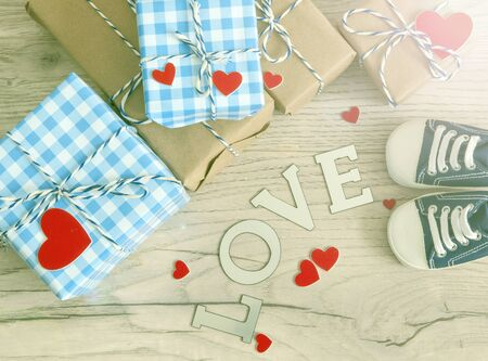 Greeting children card. Blue sneakers and gift boxeswith red heart. Top view, copy space Stock Photo