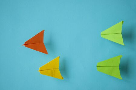 Colorful paper plane on paper background. Leadership and Business competition concepts. Copy space Stock Photo
