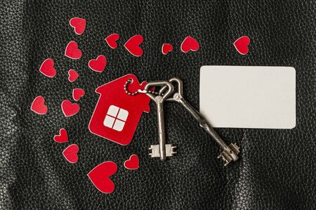 House key in heart shape with home keyring on black leather background decorated with mini heart, home sweet home concept, copy space