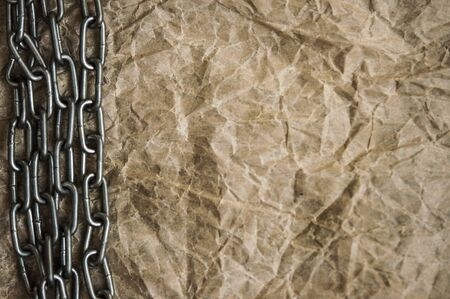 Old crumpled paper texture with metal chain