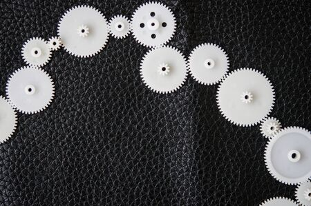 White plastic gears and cogwheels on black background
