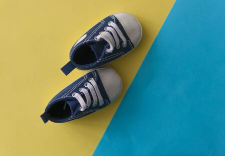 Children's denim sports shoes, stands on a colorful background with space for text. closeup view from the top. the concept of children's clothing.