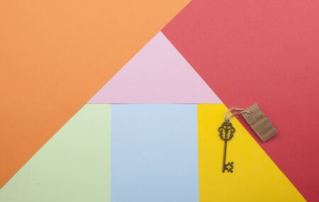 Vintage house key on colorfull paper background concept for real estate, moving home or renting property