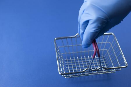 Empty supermarket trolley and woman hand in a blue medical gloves over blue background. Top view Imagens