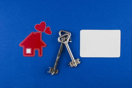 Key and house shaped keychain arrangement on blue background. Top view, flat lay. Real estate, insurance concept, mortgage, buy sell house, realtor concept