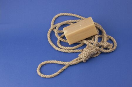 Rope with loop and brown soap on blue background. Rope with hangmans noose. Suicide concept 스톡 콘텐츠