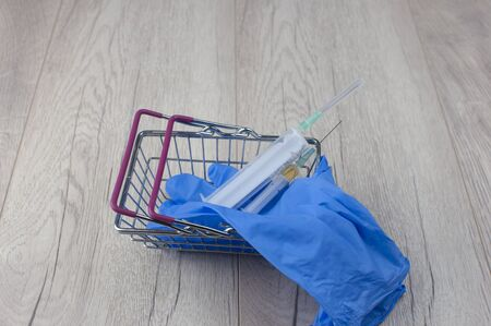 medical gloves and syringe in shopping basket on a blue background with copy space. Coronavirus, flu virus outbreak, epidemic panic, pandemic