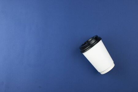 Disposable white coffee cup on blue background. Top view with copy space Imagens