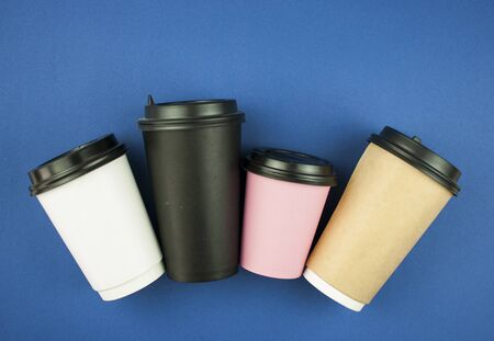 Four disposable coffee cup on blue background. Top view with copy space