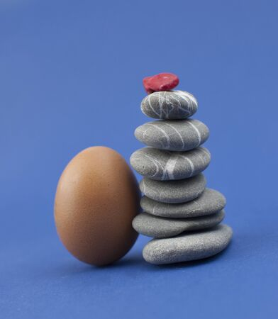 Egg with stack of sea stones on blue background. Easter holidays concept. Copyspace, place for text and wording.
