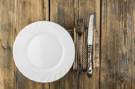 Empty white plate, knife and fork over wooden table background. View from top with copy space.