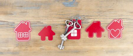 Miniature houses with vintage keys on a wood background. Real estate concept. Demand for housing. Rising and falling home prices. Copy space Фото со стока