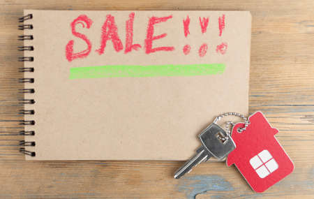 House key with home keyring, blank notebookl on wood table background, copy space