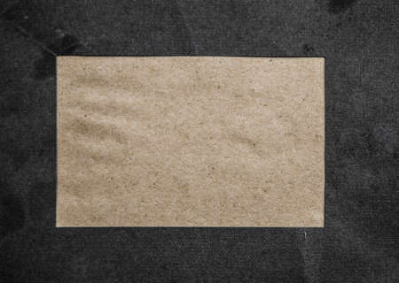 An overhead photo mockup of a square brown kraft card on a black texture, with a place for text