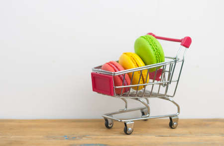 Small shopping cart with colorful macaroons on wood table over white wall Banque d'images