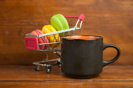 Small shopping cart with colorful macaroons on wood table over wall