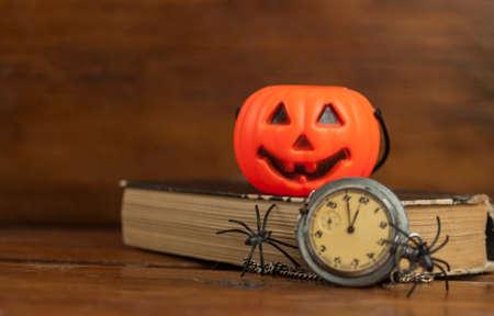 Black plastic spider sitting on pocket watch. Happy halloween