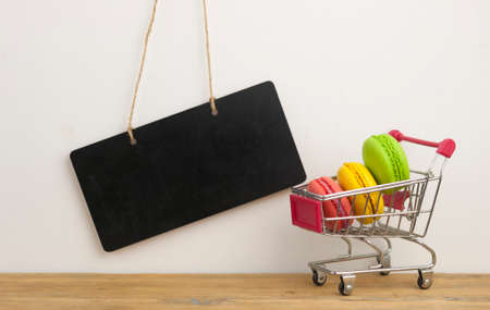 Small shopping cart with colorful macaroons on wood table over white wall and blank blackboard Banque d'images