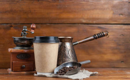 Coffee cup with coffee grinder and coffee beans on dark textured background.