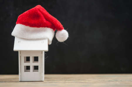 Santa hat with miniature house model on wooden table Banque d'images