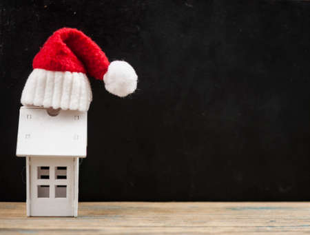 Santa hat with miniature house model on wooden table