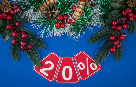Big sales 20%, twenty percents with Christmas wreath on a dark blue background, top view, copy space. Christmas big sale.