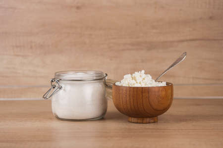 Glass jar with sugar and wooden bowl with cottage cheese on wood kitchen table Stock fotó