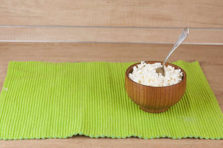 dairy product cottage cheese in brown wooden bowl with spoon on wood kitchen table