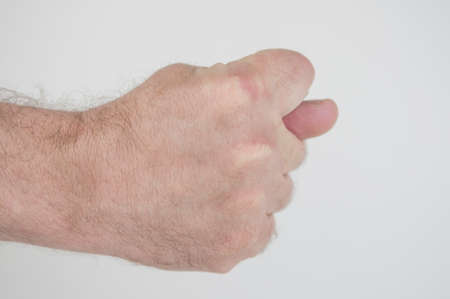 Hand showing the fig sign on white background