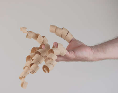 wood shavings hanging from the fingers over white background