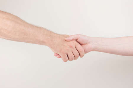 Horizontal shot of handshake between man and woman pose over white background, greet each other, shaking hands
