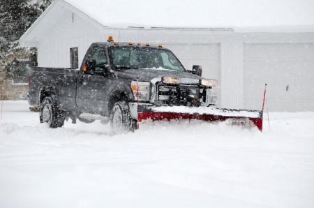눈 쟁기와 트럭은 미시간에서 겨울 날에 무거운 흰색 물건을 이동