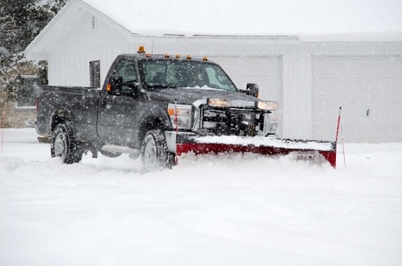 A truck with a snow plow moves the heavy white stuff on a winter day in Michigan photo