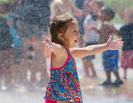 A laughing happy child plays in a summer fountain  photo