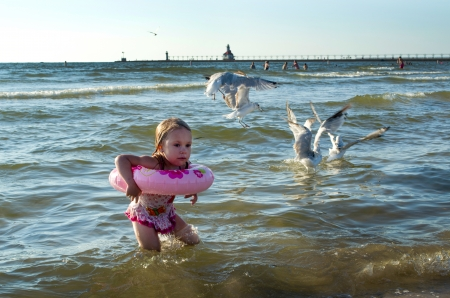 A  frightened little girl in pi nk,  struggles to get away from a close group of noisy sea gulls near the st Joseph light house in Michigan