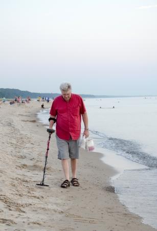 A older man searches for treasure on a michigan beach photo
