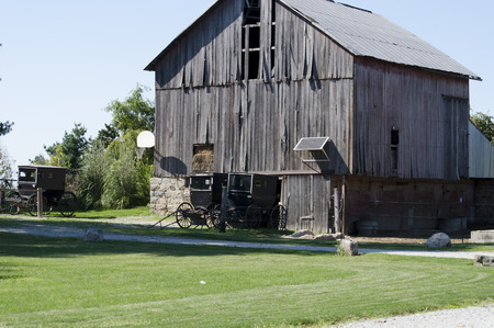 an old wood barn with a amish buggy parked outside