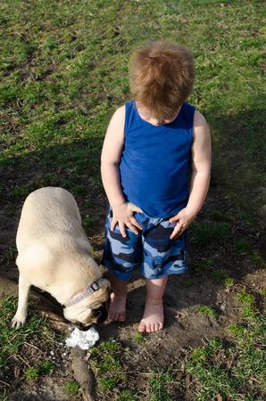 little boy watches as his dog eats his fallen ice cream photo
