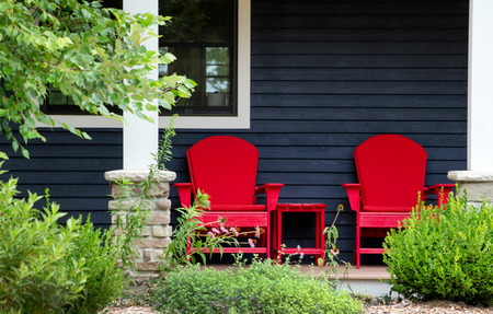 Two red adirondack chairs sit on a front porch beach house waiting for someone to sit back and relax