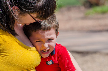 A mom consoles  her crying toddler son photo