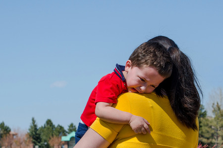 mom hugs her sad child and consoles him photo