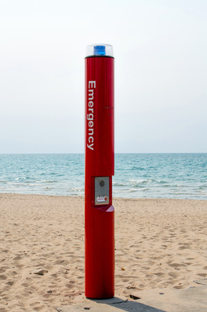 A red emergency phone on the beach has a blue flashing light attached in the event of an emergency