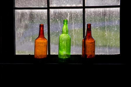 Three colorful bottles are lit up in a bright window of an old barn